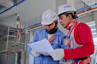 Trabalhadores utilizando EPIs analisando um papel