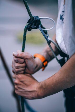 Homem manipulando equipamentos de proteção individual para trabalho em altura NR 35