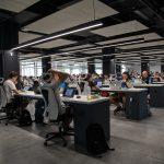 Pessoas trabalhando em uma sala grande com iluminação natural e artificial