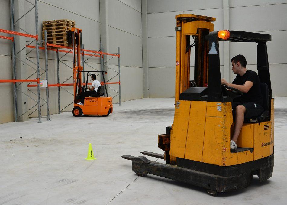 Homens operando empilhadeiras, conforme NR-12